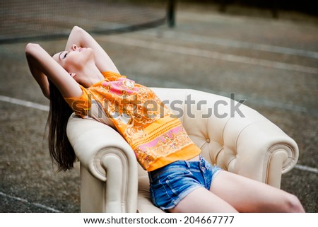 sensual elegant young woman relaxing on white leather couch outdoors - stock photo