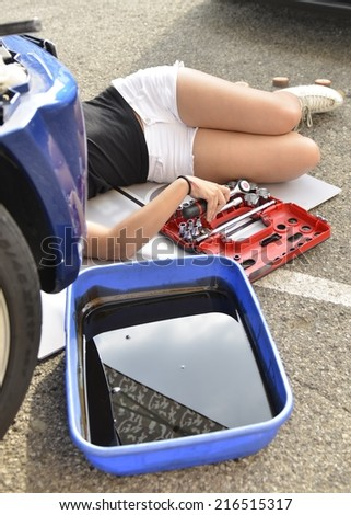 Sensual fashion woman driver with white short leggings checking level of oil on a sportive car. Mechanic girl replacing and changing motor oil in automobile engine. - stock photo