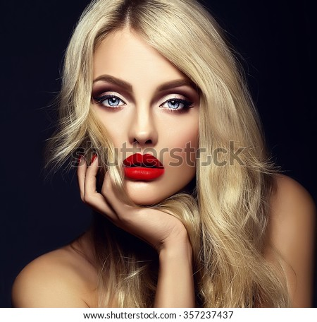 sensual glamour portrait of beautiful blond woman model lady with bright makeup and red lips touching her face , with healthy curly hair on black background  - stock photo