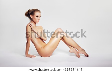 Sensual nude woman sitting on floor covering her breast with her hand and looking away at copyspace. Pretty young nude woman sitting on grey background. - stock photo