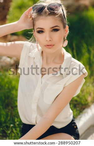 Sensual outdoor summer sunny closeup portrait of pretty young woman in sunglasses having fun outdoor on summer vacation in green park - stock photo