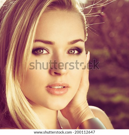 Sensual portrait of a spring woman, beautiful face, dreamy girl with pink fresh flowers outdoor, seasonal nature, tree branch and natural beauty. Photo with instagram style filters - stock photo