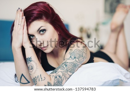 Sensual portrait of beautiful girl with tattoo lying on bed. - stock photo