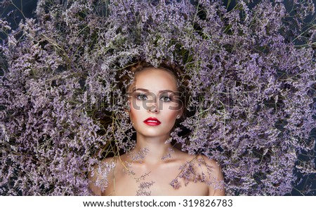 Sensual portrait of beautiful young woman with fresh clean skin and perfect make up and flower wreath in hairs. - stock photo