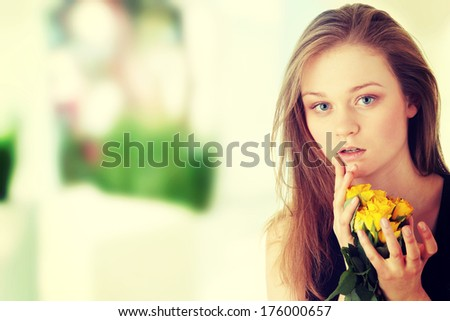 Sensual portrait of young sexy blond woman in black dress with yellow rose  - stock photo