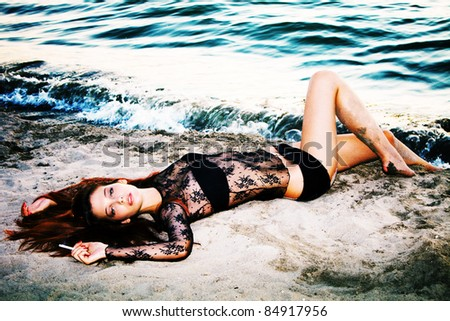 sensual redhead woman on the beach in sunset - stock photo