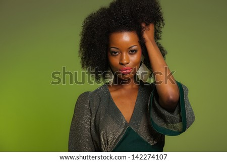 Sensual retro seventies fashion afro woman with green dress. Green background. - stock photo