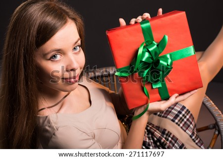 Sensual sexy attractive girl sits on a chair with a gift in her hands - stock photo