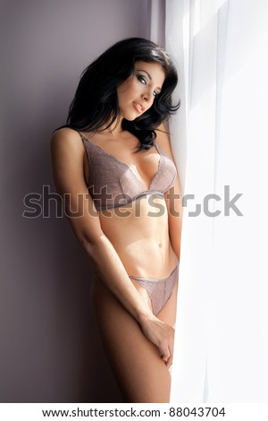 Sensual sexy woman posing in lingerie near bright window - stock photo