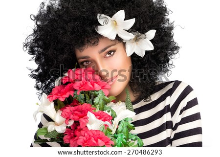Sensual spring beauty with a wild curly afro hairstyle adorned with lily flowers smiling as she nestles her cheek into a bouquet of seasonal blooms isolated on white with copy space - stock photo