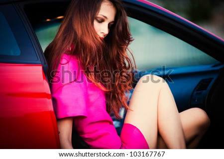 sensual stylish woman in pink dress get out from car - stock photo