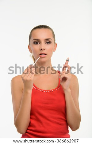 Sensual woman applying gloss on her lips. Make-up artist paints lips with gloss. Professional make-up. - stock photo