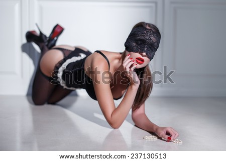 Sensual woman in black underwear and eye cover kneeling on floor with pearls - stock photo
