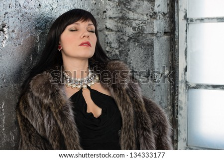 Sensual woman in fur coat standing by the window with her eyes closed - stock photo