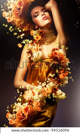 sensual woman in long yellow dress and flowers - stock photo
