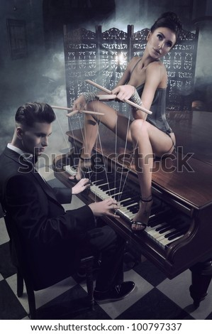 Sensual woman in sexy lingerie sitting on a piano - stock photo