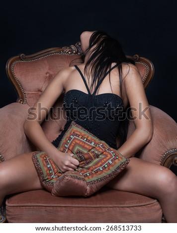 Sensual woman masturbating sitting on an armchair and  - stock photo
