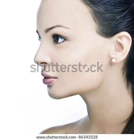 sensual woman portrait with a pearl ear ring, profile, studio shot - stock photo