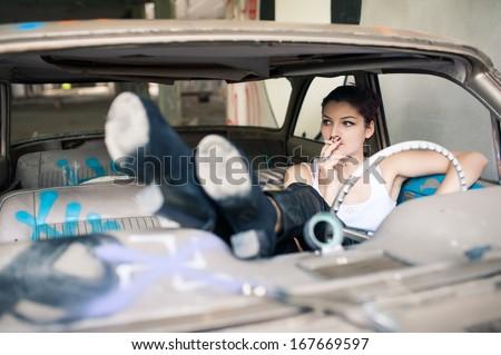 Sensual woman smoking in abandoned car.  - stock photo