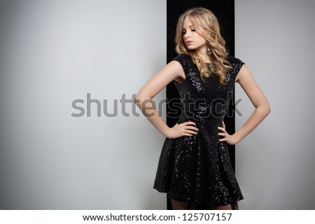 Sensual woman wearing a black dress in front of a wall - stock photo