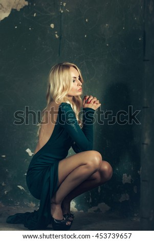 Sensual woman with attractive face blonde hair dressed in green dress with bare back sitting on haunches on dark background - stock photo