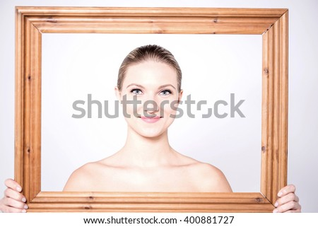 Sensual women posing from behind wooden frame - stock photo