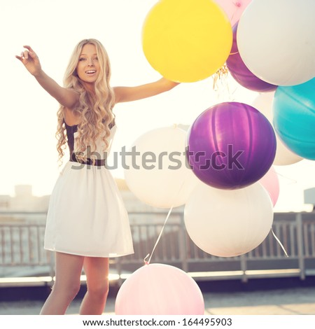 Sensual young woman enjoying witn big colorful latex balloons against the evening sun going down. Pastel colors. Outdoors, lifestyle - stock photo