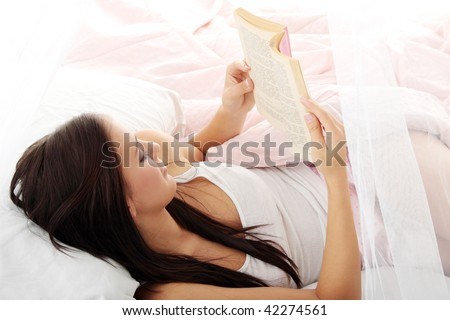 Sensual young woman laying in pink bed. Reading - stock photo
