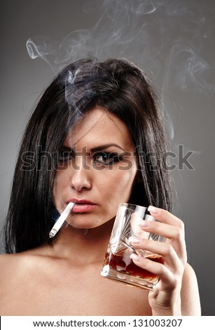 Sensual young woman smoking a cigarette and holding a glass of brandy in her hand, closeup pose on gray background, debauchery concept - stock photo