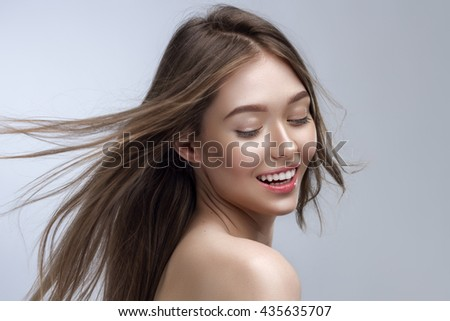 Sensual Young Woman With Beautiful Long Blond Hairs Posing On Gray Background - stock photo