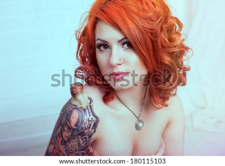 Sensual young woman with red hairs posing in studio - stock photo