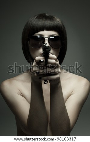 sensuality  beautifull  girl, to aim at target , with pistol, on dark background, glamour light - stock photo