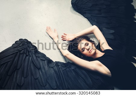 Sensuality Woman Black Angel Relaxing - stock photo