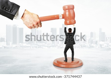 Sentence concept with businessman resists gavel at city background - stock photo