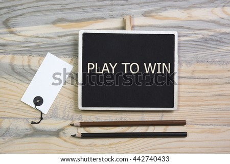 sentence play to win written with chalkboard on a table with pen.label. - stock photo