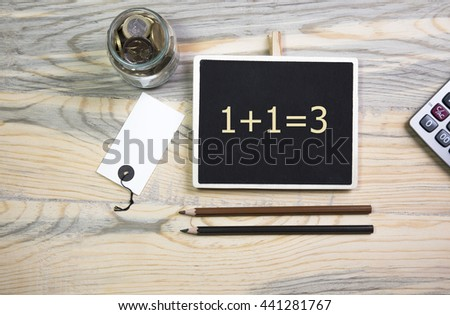 sentence 1+1=3 written on a chalkboard, on a wooden table with pen,calculator,coin - stock photo
