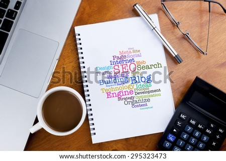 SEO cloud words on notebook with a cup of coffee, calculator, spectacle and laptop on desk - stock photo