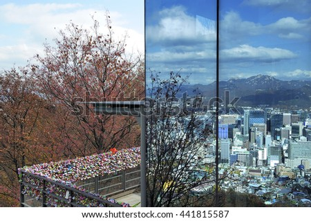 Seoul city in daylight reflected in the windows of Seoul Tower with at left love padlocks, Seoul, South Korea. - stock photo
