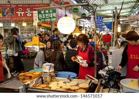 SEOUL KOREA APRIL 27: Vendors cooking traditional food for visitors at the Gwangjiang Market which is the nation's first market on april 27,2013 in  Seoul, Korea.   - stock photo