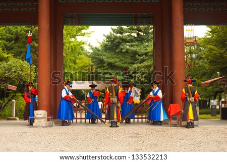 SEOUL, KOREA - AUGUST 27, 2009: Armed guards in traditional costume stand at the entry gate of Deoksugung Palace, a tourist landmark, in Seoul, South Korea on August 27, 2009. Wide - stock photo