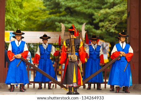 SEOUL, KOREA - AUGUST 27, 2009: Armed soldiers in period costume guard the entry gate at Deoksugung Palace, a tourist landmark, in Seoul, South Korea on August 27, 2009 - stock photo