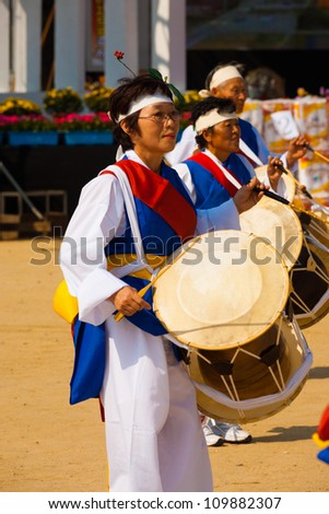 SEOUL, KOREA - SEPTEMBER 18: An unidentified Korean woman dressed in festive traditional clothes beats her janggu drums at a local outdoor festival on September 18, 2009 in Seoul, Korea - stock photo