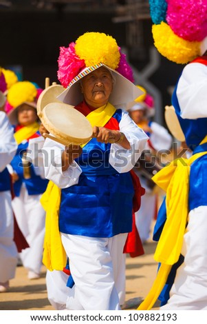 SEOUL, KOREA - SEPTEMBER 18: An unidentified mature woman plays a handheld traditional Korean drum in colorful clothes at a local outdoor festival on September 18, 2009 in Seoul, Korea - stock photo