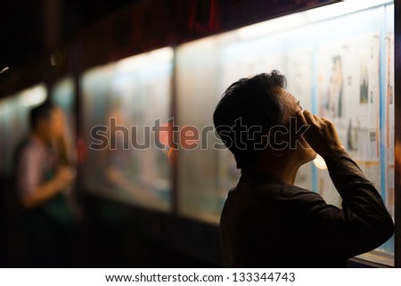 SEOUL, KOREA - SEPTEMBER 11, 2009: Unidentified men read a public newspaper at night displayed outside of the Korea Press Foundation in Seoul, South Korea on September 11, 2009 - stock photo