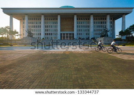 SEOUL, KOREA - SEPTEMBER 8, 2009: Unidentified policemen bicycle in front of the National Assembly building, home to the legislative branch of government, in Seoul, South Korea on September 8, 2009 - stock photo
