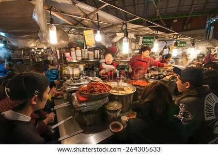 SEOUL, SOUTH KOREA - FEBRUARY 28, 2015 : People enjoying street food at Gwangjang Market.The market was established in 1905 .It has many restaurants and food stalls selling traditional Korean cuisine. - stock photo