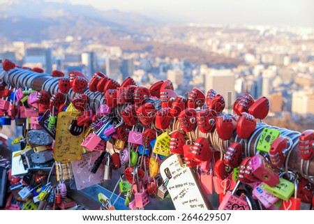 Seoul, South Korea - NOV 9: As a sign of devotion, couples write their names on locks and clip them to a wall at Namsan Tower in Seoul, South Korea. on November 9, 2014 - stock photo