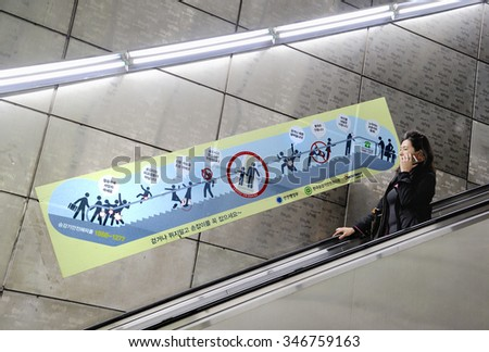 SEOUL, SOUTH KOREA - NOVEMBER 10 : Lady at escalator of Metropolitan Subway in Seoul, one of the most heavily used underground system in the world. November 10, 2015, Seoul, South Korea. - stock photo