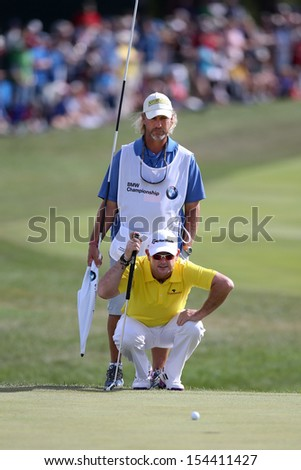 Sep 15, 2013; Lake Forest, IL, USA; Rory Sabbatini (bottom) and his caddie Kevin Fasbender line up a putt on the 18th green during the third round of the BMW Championship at Conway Farms Golf Club. - stock photo