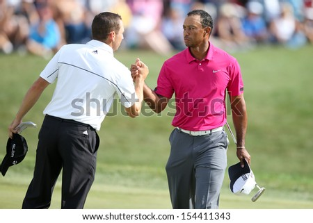 Sep 15, 2013; Lake Forest, IL, USA; Tiger Woods (r) shakes hands with Sergio Garcia on the 18th green after the third round of the BMW Championship at Conway Farms Golf Club. - stock photo